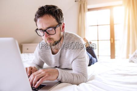 man lying on bed using laptop