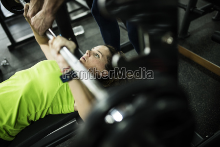 woman training bench press at gym