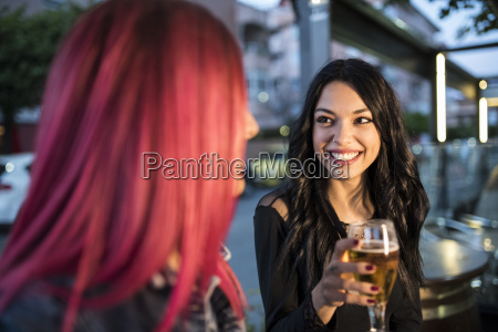 two friends sitting in bar drinking