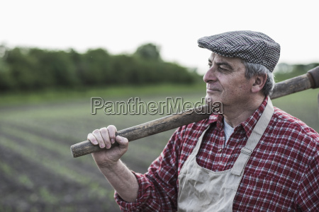 farmer holding tool in front of
