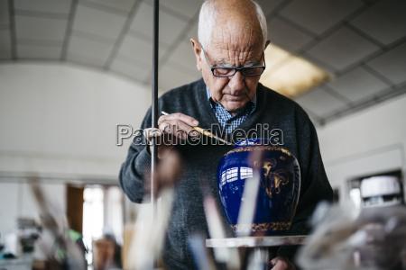 senior man decorating ceramic vase in