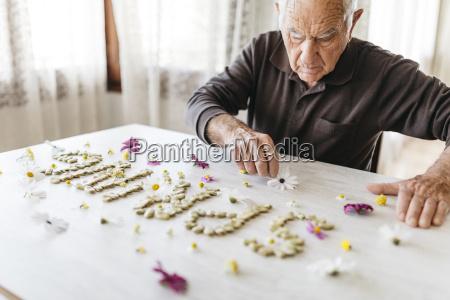 senior man shaping the word spring