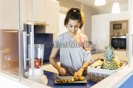 young woman in kitchen preparing fruit