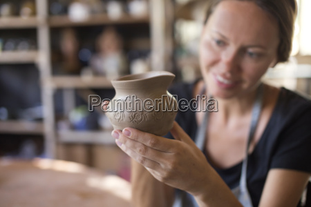 smiling potter in workshop looking at
