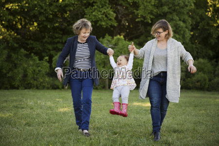 mother and grandmother swinging toddler in