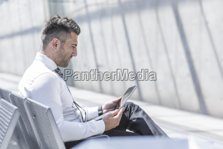 businessman using digital tablet at waiting