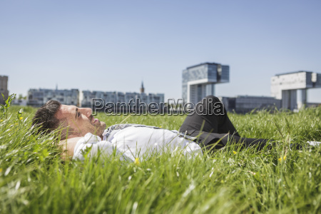 germany cologne smiling businessman lying in