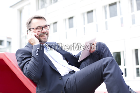 smiling businessman on the phone outdoors