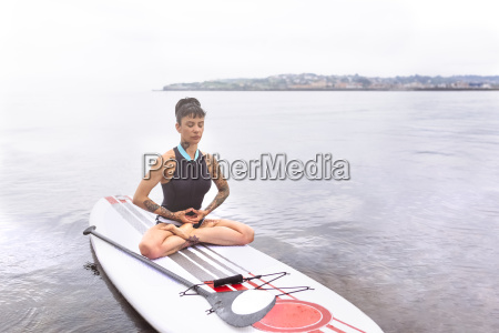 woman practicing paddle board yoga