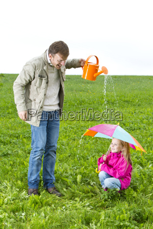 father with watering can and daughter
