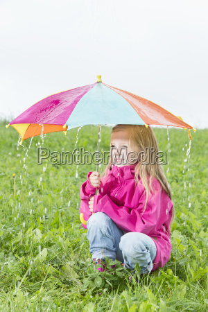 young girl crouching with umbrella on