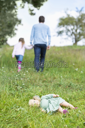 doll lying on meadow while man