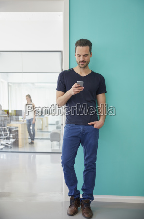 man standing in office using smart