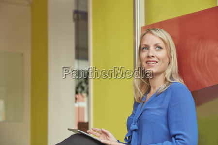 woman sitting in office using digital
