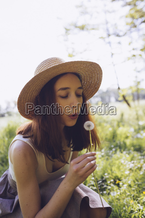 young woman on a meadow blowing