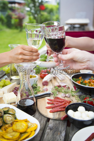 people clinking wine glasses and enjoying