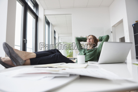 businesswoman relaxing at office desk