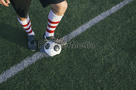 legs of football player with ball