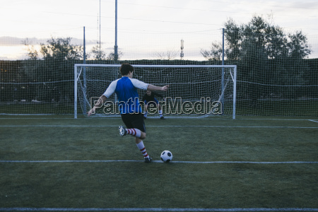 football player kicking a ball in