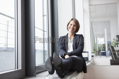 relaxed businesswoman sitting at the window