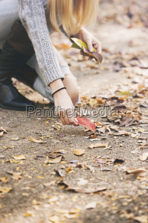teenage girl collecting autumn leaves