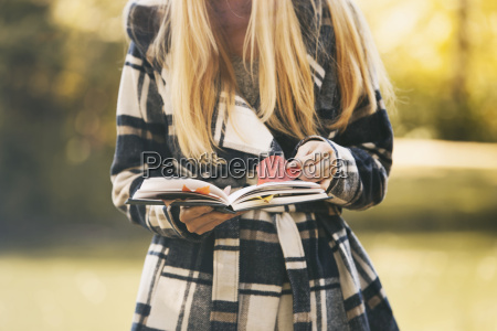 teenage girl holding book and autumn