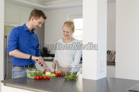 couple in kitchen preparing a salad