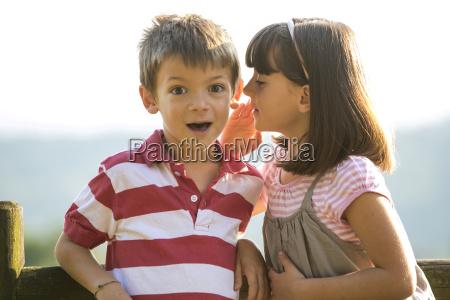 little girl whispering secret in the