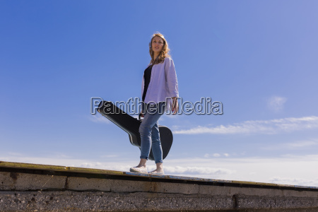 young woman with guitar case on