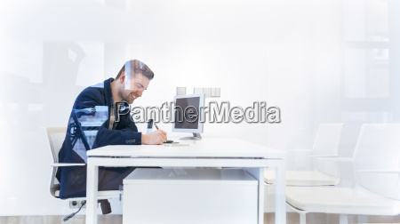 smiling young man working at desk