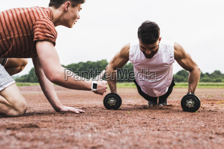athlete doing pushups with dumbbells on