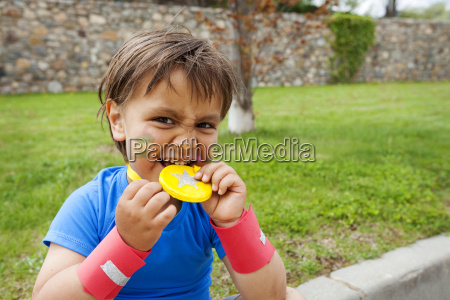 little boy biting on medal