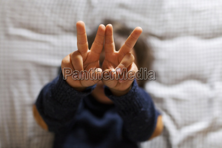 little boy making victory sign with