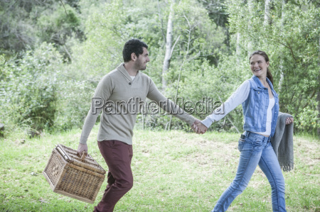 young couple with picnic basket walking