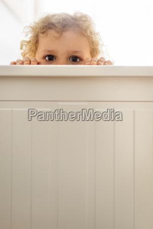 little boy hiding behind wooden wall
