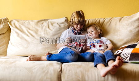 two smiling boys sitting on couch