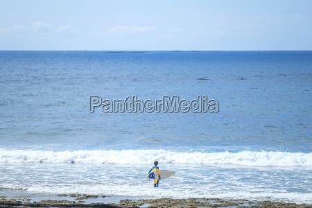 spain tenerife boy with surfboard in