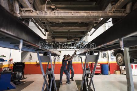 car mechanics working under a car