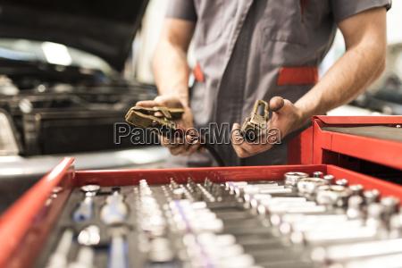 detail of hands with tweezers to