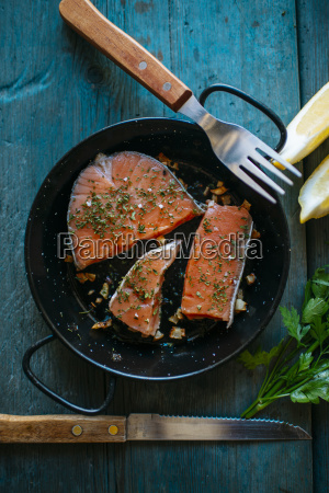 salmon fillets in pan with parsley