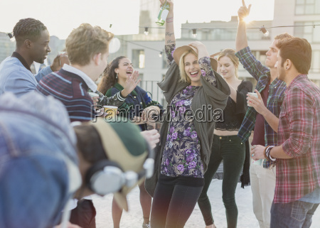 playful young adult friends dancing at