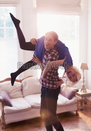 portrait playful husband carrying wife over