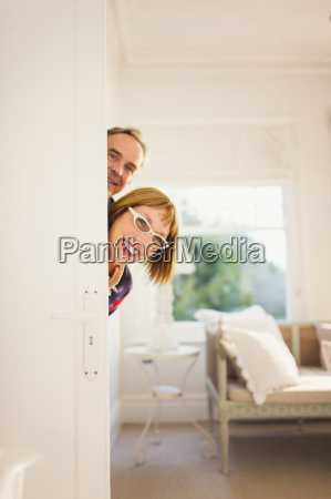 portrait playful mature couple peering from