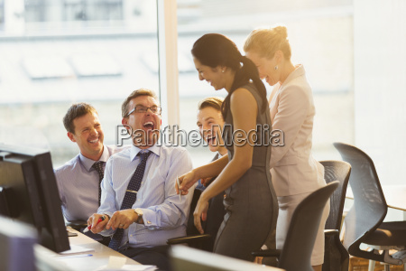 laughing business people at computer in