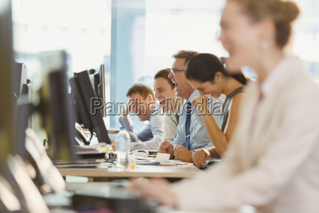 business people laughing at desk in