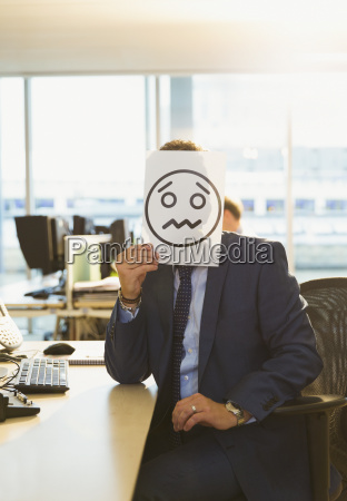 portrait of businessman holding frowning face