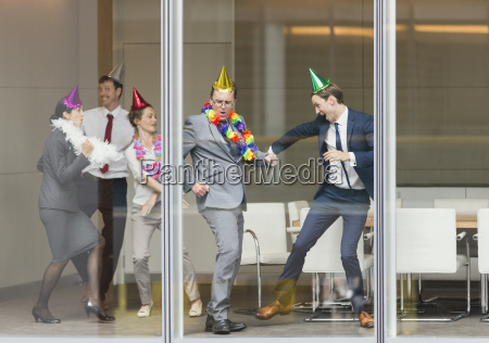 playful business people in party hats
