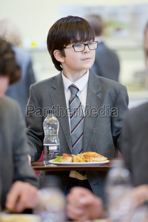 middle school student eating lunch looking