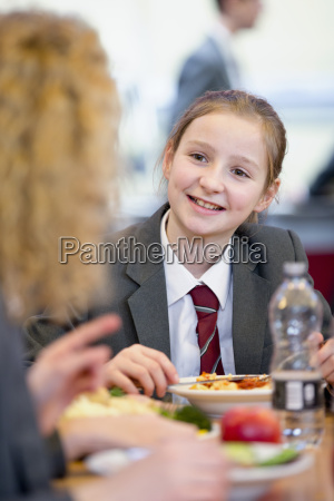 smiling middle school student eating lunch