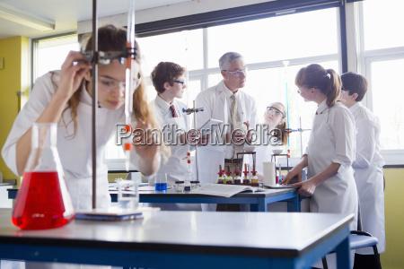chemistry teacher guiding high school students